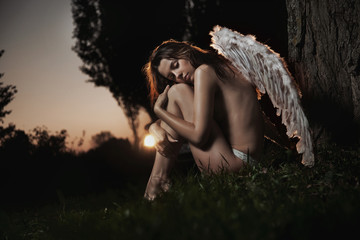 Female angel posing over an autumn sunset