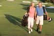 Leinwandbild Motiv Senior Couple Walking Along Golf Course Carrying Bags