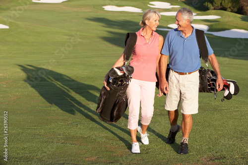 Fotobehang Golf Senior Couple Walking Along Golf Course Carrying Bags