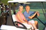 Senior Couple Riding In Golf Buggy On Golf Course