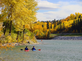 Kayakers on a river surrounded by colorful fall foliage
