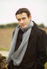 Junger Mann im Mantel mit Schal