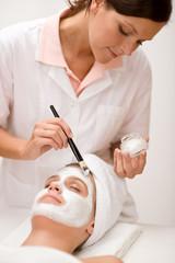 Woman at spa getting facial mask