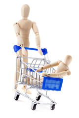 One wooden dummy rolls another in the shopping cart.