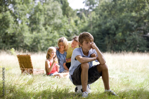 young boy sitting on a football looking bored