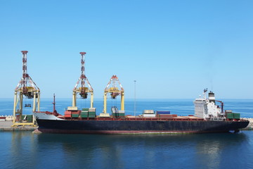 merchant ship with cargos on board at its moorings in port.