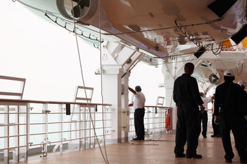 service staff in black uniform standing on cruise liner deck