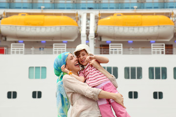 mother carrying her daughter and laughing, big cruise ship