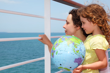 mother and daughter on cruise liner deck, child holding globe