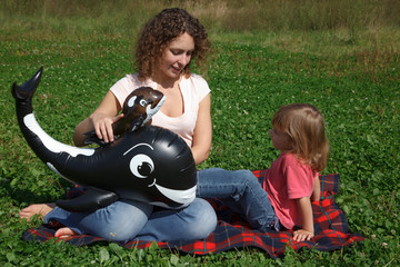 Mom and daughter play on grass with inflatable toys.