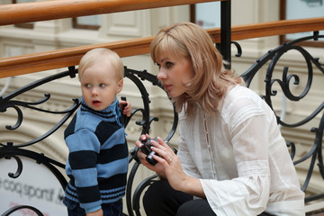woman and boy indoors with camera in hands
