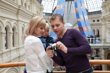 Man shows girl with baby picture with digital camera.