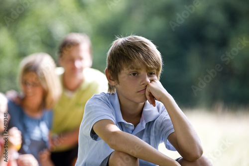 A family having a picnic, young boy looking bored