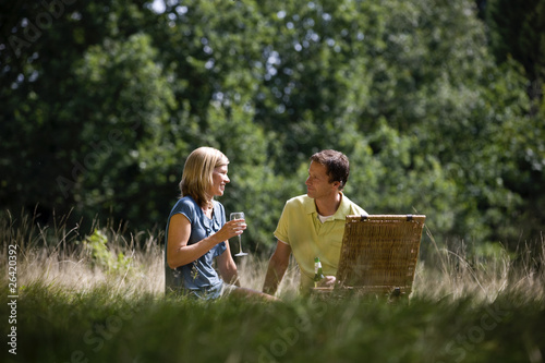 A middle aged couple sitting on the grass, having a drink