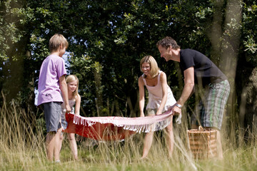 A family laying a picnic blanket on the grass