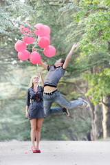 young guy is flying away, girl is holding him