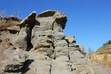 Grey sandstone deposits against a blue sky poster