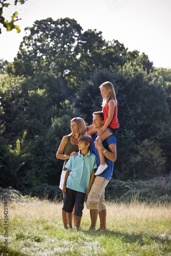 A family standing in a park, father carrying his daughter