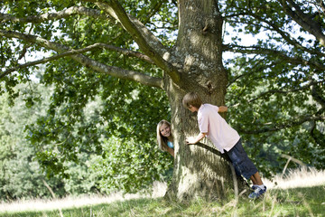A young boy and girl playing hide and seek