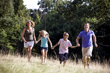 A family running through a field, holding hands