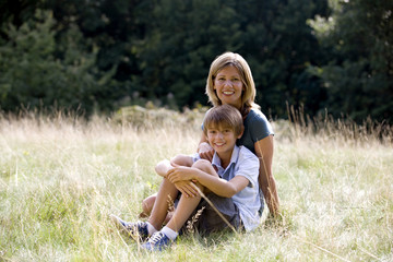 A mother and son sitting on the grass