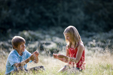 A young boy and girl sitting in long grass