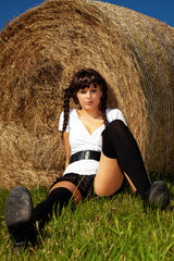 Junge hübsche Frau sitzt vor Heuballen 917