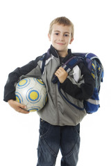 Happy young school boy holding a football ball