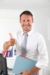 Happy businessman with thumb up in the office