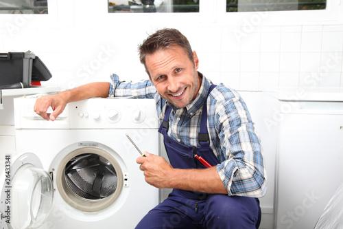 Plumber fixing broken washing machine - 26433341