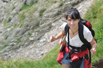 happy brunette young woman equipped for hiking.