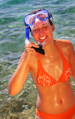 Pretty young woman in orange bikini with diving goggles