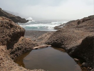 A tidal pool with waves crashing in the background