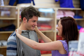 cheerful couple choosing clothes standing in the men department