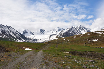Colorful mountains with road, snow, sky and clouds