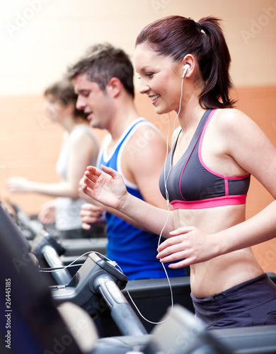 Beautiful female athlete standing on a running machine listening
