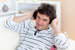 funny man listening music with headphones on sitting in his livi