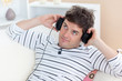 thoughful man listening music looking the top sitting in the sof