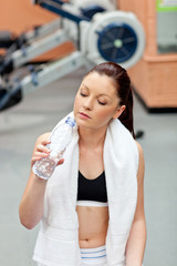 cute athletic woman drinking water after exercises in a fitness