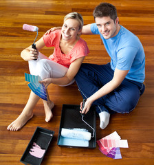 Young couple sitting on floor smiling