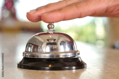Leinwanddruck Bild Hand of a man using a hotel bell - a series of HOTEL images.
