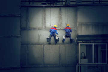 Painters in hard hats and harnesses hanging building wall