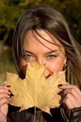 Beautiful young woman holding a maple leaf. portrait.