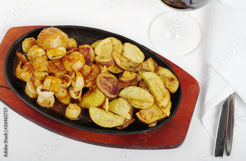 Seafood and fried potatoes with wine and cutlery