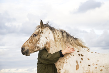 Woman hugging an appaloosa horse