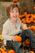 Little boy in pumpkin patch holding pumpkin in the fall
