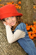 Young girl with a hat in a pumpkin patch in the fall