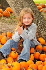 Little blonde girl in a pumpkin patch in the fall