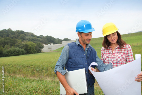 Business people checking plan on construction site