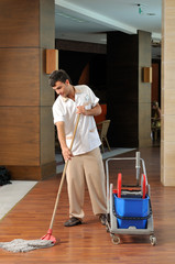 Young housekeeper mobbing the floor - a series of HOTEL images.